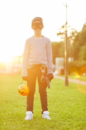 Full length portrait of teenage boy wearing Halloween costume looking at camera while posing outdoors lit by sunlight and holding trick or treat basket, copy space