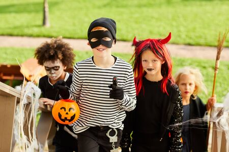 Multi-ethnic group of children trick or treating on Halloween standing on stairs in row, focus on smiling boy wearing costume and holding pumpkin basket