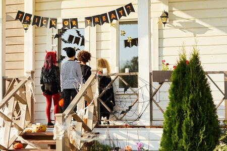 Back view of children trick or treating on Halloween, kids standing on porch knocking on doors of decorated house, copy space