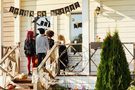 Vista posterior de los niños con truco o trato en Halloween, niños de pie en el porche llamando a las puertas de la casa decorada, espacio de copia