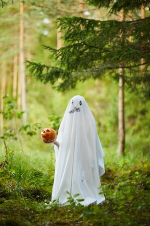 Full length portrait of spooky child dressed as ghost holding pumpkin while posing in forest on Halloween, copy space Фото со стока