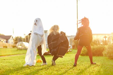Full length portrait of happy children wearing costumes running on green lawn while having fun on Halloween and playing games in sunlight, copy space Фото со стока