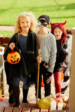Full length portrait of children trick or treating on Halloween standing on stairs in row, focus on happy girl holding pumpkin basket