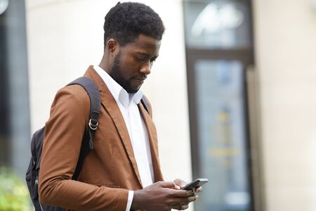 Waist up portrait of trendy African-American man using smartphone while standing outdoors in city street, copy space