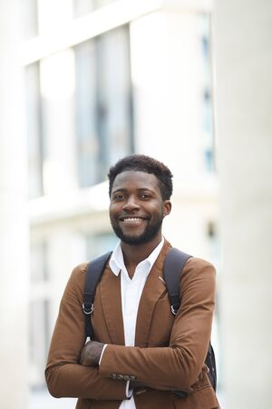 Waist up portrait of confident African-American man smiling happily at camera while standing with arms crossed in city street, copy space