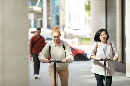 Portrait of two women riding electric scooters while commuting in urban city, copy space