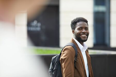 Waist up portrait of young African-American man smiling happily at camera while standing outdoors ion city street, copy space Фото со стока
