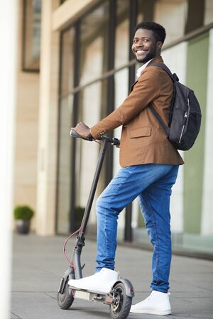 Full length portrait of trendy African businessman riding electric scooter and smiling at camera while posing outdoors in city street