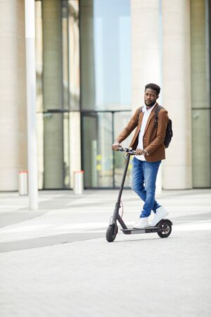 Full length portrait of trendy African man riding electric scooter and looking at camera while commuting in city street, copy space