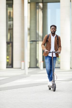 Full length portrait of contemporary African-American man riding electric scooter and looking at camera while commuting in city streets, copy space 版權商用圖片 - 130072387