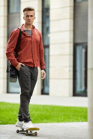 Full length portrait of contemporary young man skateboarding in city street and looking at camera, copy space