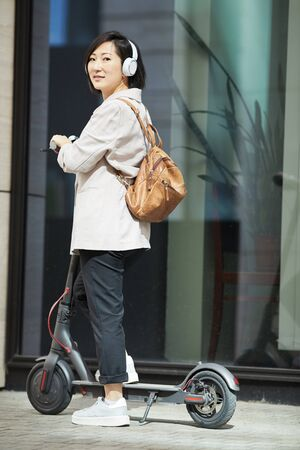 Full length portrait of contemporary Asian woman riding electric scooter and looking at camera while posing in urban setting, copy space