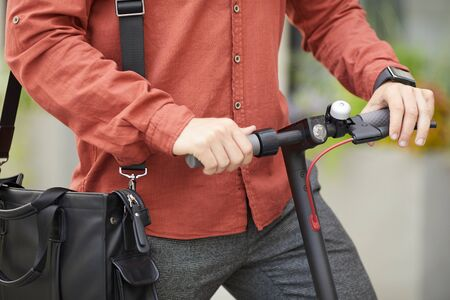 Closeup of contemporary young man riding electric scooter in city street, focus on male hands holding handlebars, copy space