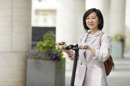 Waist up portrait of smiling Asian woman riding electric scooter looking at camera while posing in city street, copy space 版權商用圖片