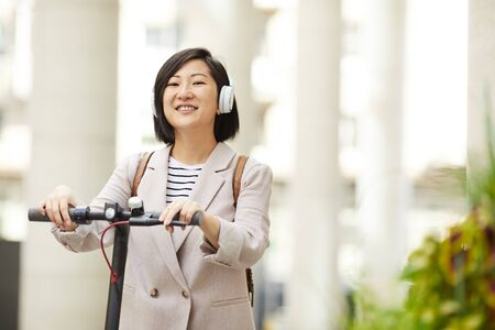 Waist up portrait of adult Asian woman riding electric scooter and smiling happily at camera in city street, copy space