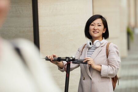 Waist up portrait of young Asian woman riding electric scooter and looking at camera while posing outdoors in city street, copy space Imagens