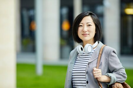 Waist up shoulders portrait of modern Asian woman looking at camera while posing outdoors in city street, copy space
