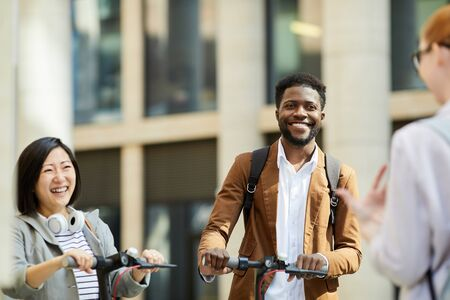 Multi-ethnic group of cheerful young people riding electric scooters in city street and meeting friends, copy space Imagens