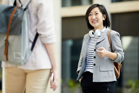 Portrait of contemporary Asian woman smiling happily while meeting friend outdoors in city street, copy space Imagens