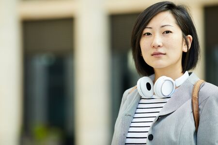 Head and shoulders portrait of modern Asian woman looking at camera while posing outdoors in city street, copy space Imagens