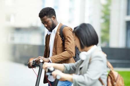 Side view portrait of two people riding electric scooters in city street, focus on African-American man in background, copy space