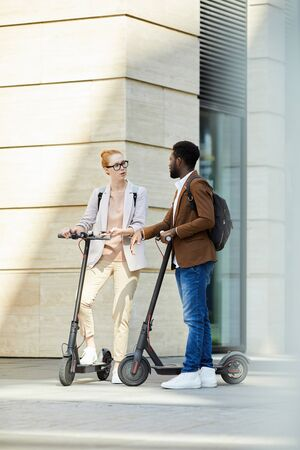 Full length portrait of modern young couple riding electric scooters in city street and chatting, copy space
