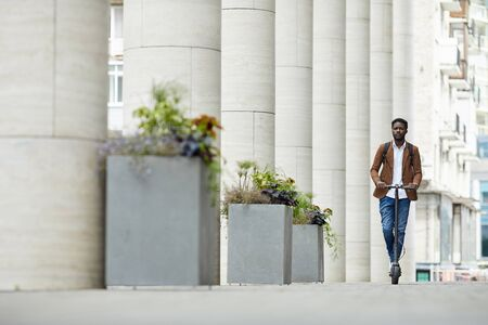 Wide angle portrait of contemporary African man riding electric scooter in city street going towards camera, copy space