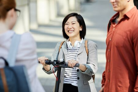 Group of contemporary young people chatting in city street, focus on Asian woman smiling happily, copy space Imagens