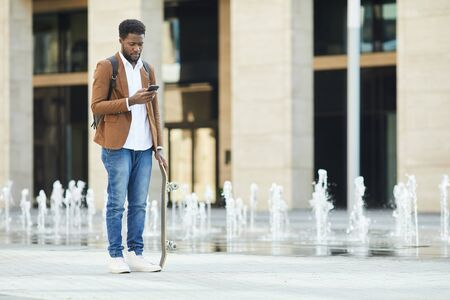 Full length portrait of young African-American man typing text message via smartphone while standing with skateboard in urban setting, copy space Фото со стока