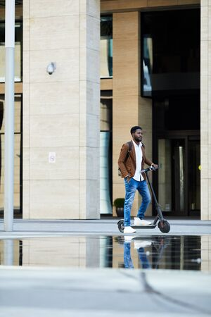 Full length portrait of contemporary African-American man riding electric scooter in urban setting outdoors, copy space
