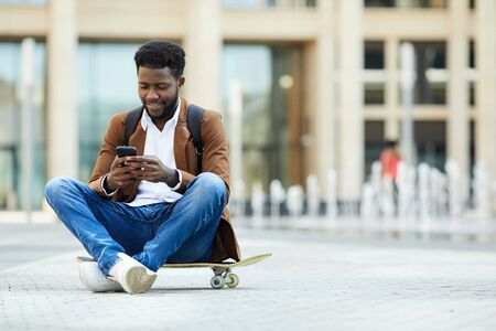 Full length portrait of contemporary African-American man using smartphone and smiling while sitting cross legged on skateboard outdoors, copy space
