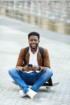 Full length portrait of contemporary African-American man using smartphone and smiling at camera while sitting cross legged on skateboard outdoors, copy space