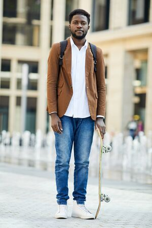 Full length portrait of young African-American man looking at camera while posing with skateboard in urban setting, copy space