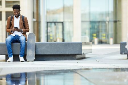 Full length portrait of young African-American man typing text message via smartphone while sitting outdoors in urban setting, copy space background Фото со стока