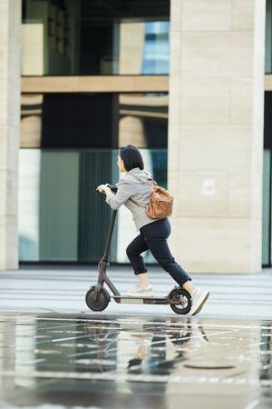 Full length side view of young Asian woman riding electric scooter fast in city street, copy space