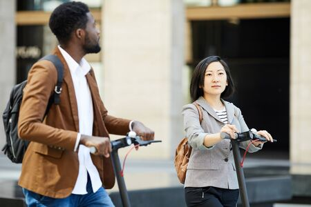 Waist up portrait of Asian woman riding electric scooter in street together with African man, copy space