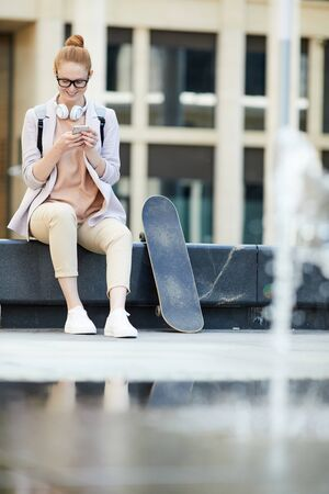 Full length portrait of contemporary young woman using smartphone and smiling happily while relaxing on bench in urban setting, copy space Фото со стока