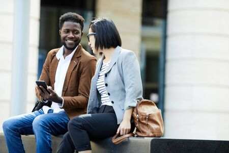 Portrait of two young business people relaxing outdoors during break, African man and Asian woman chatting happily, copy space