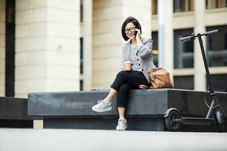 Full length portrait of smiling Asian woman speaking by smartphone outdoors with electric scooter in foreground, copy space