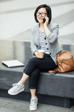 Full length portrait of modern Asian woman speaking by smartphone outdoors and smiling happily, scene in urban setting