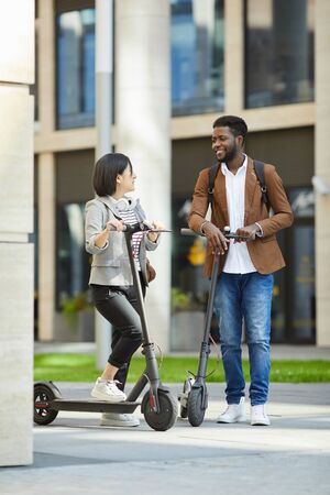 Full length portrait of contemporary young couple riding electric scooters in city street and smiling happily looking at each other, copy space