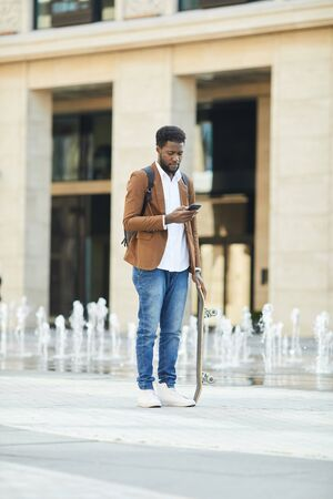 Full length portrait of young African-American man typing text message via smartphone standing in urban setting by street fountain, copy space