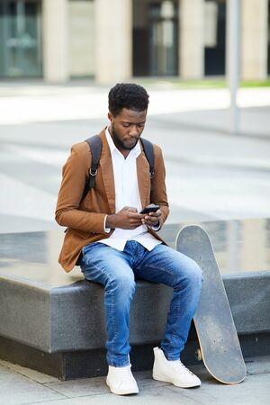 Full length portrait of young African-American man typing text message via smartphone while sitting outdoors in urban setting, copy space
