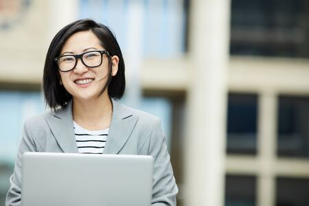 Waist up portrait of modern Asian woman using laptop outdoors and smiling happily at camera, copy space