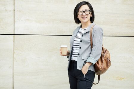Waist up portrait of smiling Asian woman posing with backpack and coffee cup while standing against concrete wall in college campus, copy space