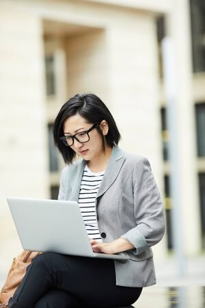 Portrait of modern Asian woman using laptop outdoors sitting on bench in urban setting and looking at screen, copy space