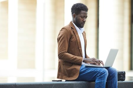 Side view portrait of young African-American man using laptop outdoors while working on business project in urban setting, copy space