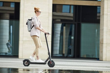 Side view full length of modern young woman riding electric scooter while commuting to work in city, copy space