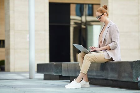 Side view portrait of red haired young woman using laptop outdoors while working on business project using wi-fi, copy pace Фото со стока