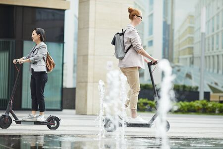 Full length portrait of people commuting in city, focus on young woman riding electric scooter in foreground, copy space